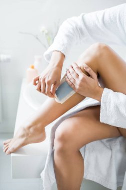 partial view of young adult woman waxing leg with depilation stripe in bathroom