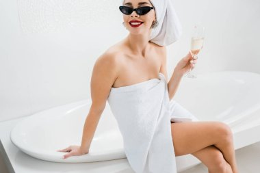 Beautiful and smiling woman in sunglasses and towels holding champagne glass and looking away in bathroom stock vector