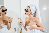 szelektív összpontosít, vonzó nő, napszemüveg és törölközők gazdaság üveg pezsgőt, és nézett tükörbe