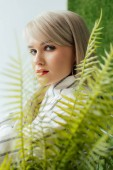 Fotografie beautiful stylish blonde girl looking at camera and posing near fern leaves