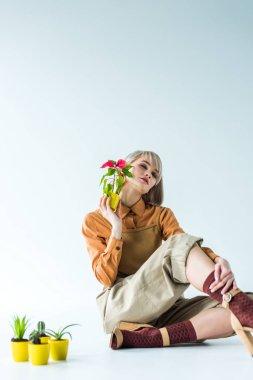 beautiful stylish girl with eyes closed holding flower pot and posing isolated on white