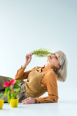 beautiful stylish girl holding fern leaves and posing isolated on white with copy space
