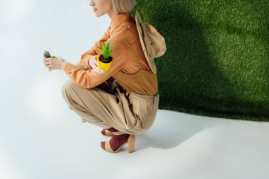 partial view of stylish girl holding flower pots on grey with green grass