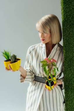 beautiful stylish young woman holding flower pots on grey with green grass
