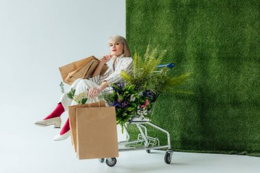 beautiful stylish girl sitting in cart with fern, flowers and shopping bags on white with green grass