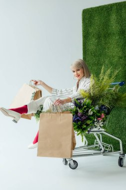 beautiful stylish girl looking at camera while sitting in cart with fern, flowers and shopping bags on white with green grass