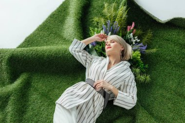 beautiful fashionable girl lying on artificial grass with fern and flowers