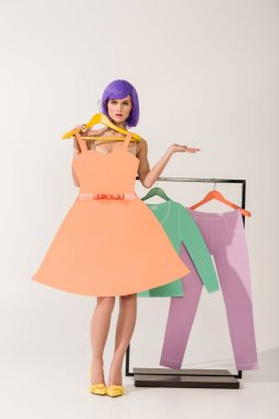 beautiful surprised girl with purple hair holding paper dress and posing near rack with colorful clothes on white