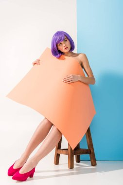 beautiful young woman with purple hair covered in coral paper sheet sitting on chair while posing on blue and white