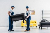 Fotografia two movers in uniform transporting furniture in apartment
