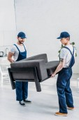 two movers in uniform transporting furniture in apartment
