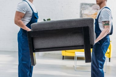 cropped view of two movers in uniform transporting furniture in apartment