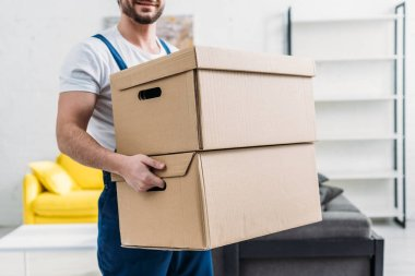 cropped view of mover in uniform carrying cardboard boxes in apartment