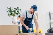 Mover in gleichmäßiger Packkarton mit Klebeband in Wohnung