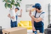 Mover csomagolás karton doboz cellux és integetett kollégája a lakásban