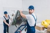 dva šikovní hybři používající ruční vozík při přepravě chladničky v bytě