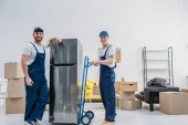 Fotografia two smiling movers using hand truck while transporting refrigerator in apartment