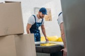 selective focus of movers wrapping furniture with roll of stretch film in apartment