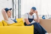 Zwei Mover in Uniform sitzen auf Couch in Wohnung