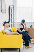 két mozgatói egységes ülve a kanapén az apartmanban