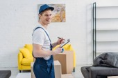 handsome mover holding clipboard and looking at camera near cardboard boxes in apartment