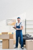 mover looking at camera and holding clipboard near cardboard boxes in apartment with copy space