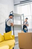 Zwei Mover in gleichmäßiger Transportwantel in Wohnung