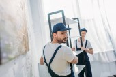 Photo two movers in uniform transporting rack in apartment with copy space