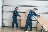 two movers in uniform using hand trucks while transporting cardboard boxes in warehouse