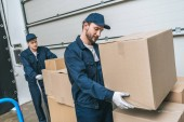 Fotografie two concentrated movers in uniform transporting cardboard boxes in warehouse