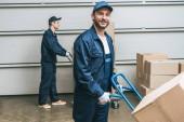 Fotografia due motori in scatole di cartone trasporto uniforme con carrelli a mano in magazzino