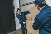 two movers in uniform using hand truck while transporting cardboard boxes in warehouse with copy space