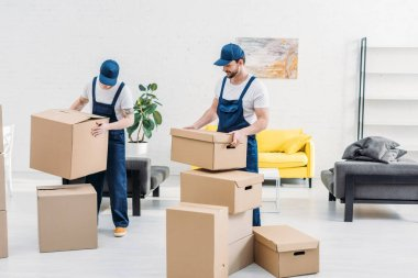 Two movers in uniform carrying cardboard boxes in modern apartment stock vector