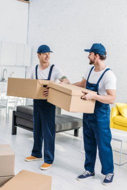 Two smiling movers transporting cardboard boxes in apartment stock vector