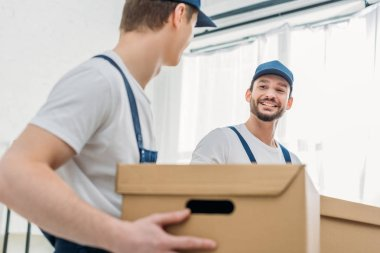 selective focus of two movers transporting cardboard boxes in apartment