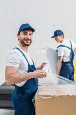 handsome mover in uniform looking at camera while wrapping cardboard box with stretch film in apartment