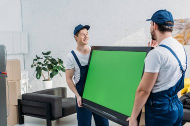 Two movers in uniform transporting tv with green screen in apartment stock vector