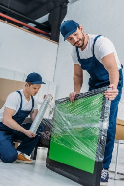 two movers using roll of stretch film while wrapping tv with green screen in apartment