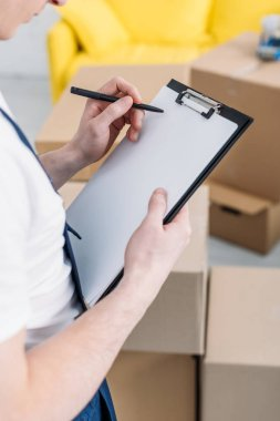 Cropped view of mover writing in empty clipboard near cardboard boxes in apartment stock vector