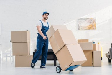 mover in uniform transporting  cardboard boxes on hand truck in apartment