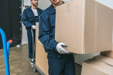 cropped view of two movers in uniform transporting cardboard boxes with hand truck in warehouse