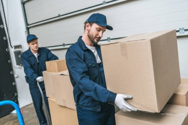 two concentrated movers in uniform transporting cardboard boxes in warehouse