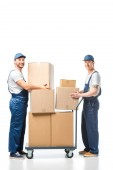 Fotografia two handsome movers looking at camera while transporting cardboard boxes with hand truck on white