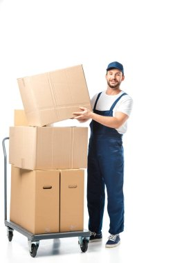 Handsome mover in uniform transporting cardboard box near hand truck with packages isolated on white stock vector