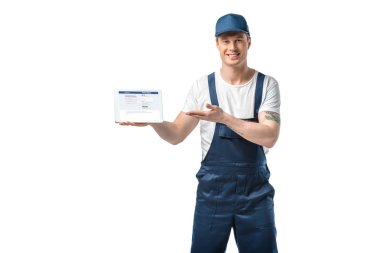 handsome smiling mover gesturing with hand while presenting digital tablet with facebook app on screen isolated on white