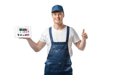 handsome smiling mover showing thumb up and presenting digital tablet with aliexpress app on screen isolated on white