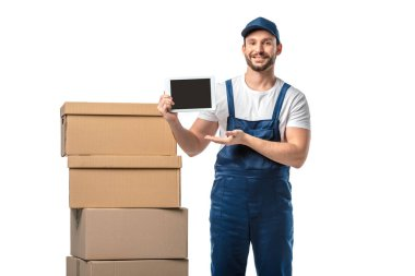 mover with cardboard boxes looking at camera and presenting digital tablet with blank screen isolated on white