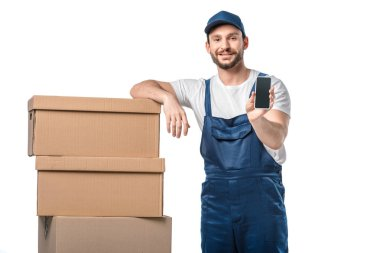 handsome smiling mover with cardboard boxes presenting smartphone with blank screen isolated on white