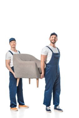 two smiling movers looking at camera and transporting grey armchair isolated on white