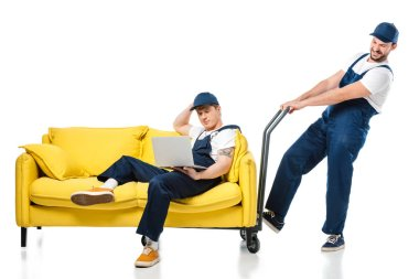 mover in uniform sitting on sofa and using laptop while colleague pushing hand truck on white